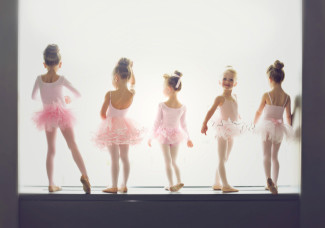 5 baby ballerinas standing in a window with one turning around smiling at the camera