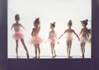 five Baby ballerinas standing with their backs facing the camera in a windwo