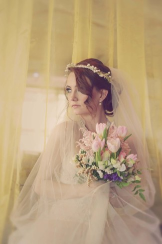 bride wearing a chapel length veil wrapped around, a crown and holding tulip bouquet