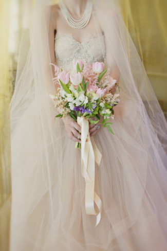 bride wearing a chapel length veil falling forward draped around her and a pearl necklace