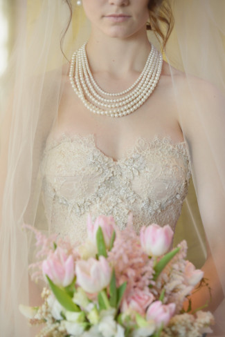 bride wearing a pearl necklace with her veil draped around her