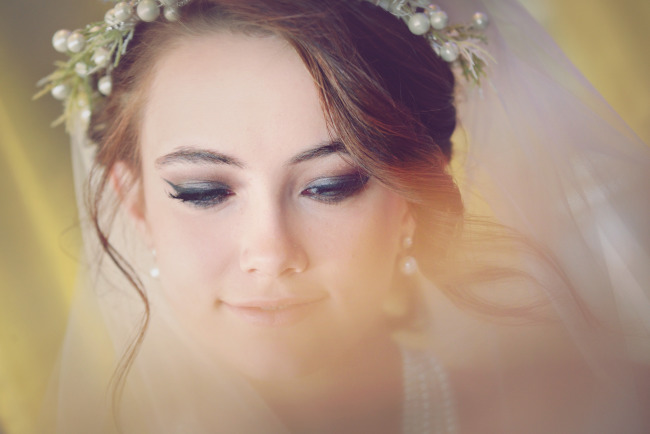 bride wearing a berry crown and veil with curls falling around her face