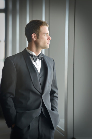 Groom looking out the window wearing a traditional tux