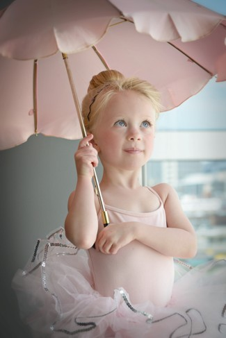 Baby ballerina holding a umbrella and wearing a pink tutu