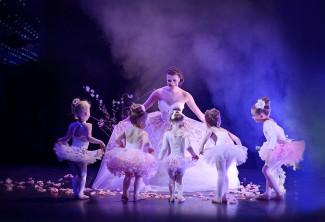 baby ballerinas surround ballerina bride on stage