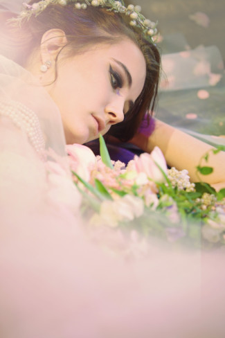 bride laying on the ground with rose petals wearing a berry crown
