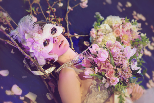 bride laying on the ground wearing a pearl necklace and a mask with a feather and flowers