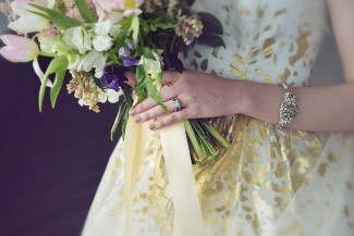 bride wearing a white gown with speckled gold spots holding a bouquet of pink tulips