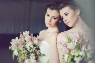 bride wearing a strapless gown and holding pink tulip bouquet leaning up against a mirrior