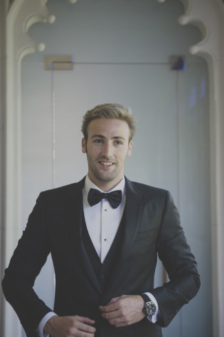 Groom wearing a classic black tux and bow tie