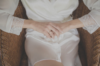 bride sitting in a wicker chair in a silk robe and clasping her hands
