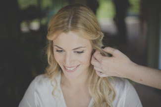 Blond bride getting her hair done while smiling wearing a white silk robe