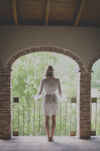 Bride wearing a white silk robe looking out on a balcony