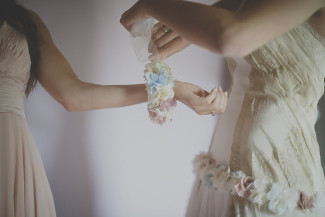 bride tying a flower bracelet around bridesmaids wrist