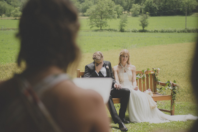 Bride and groom sitting on bench during open air rustic wedding ceremony