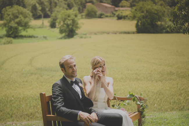 bride and groom sitting on wooden bench during wedding ceremony with big smiles; bride wiping tears