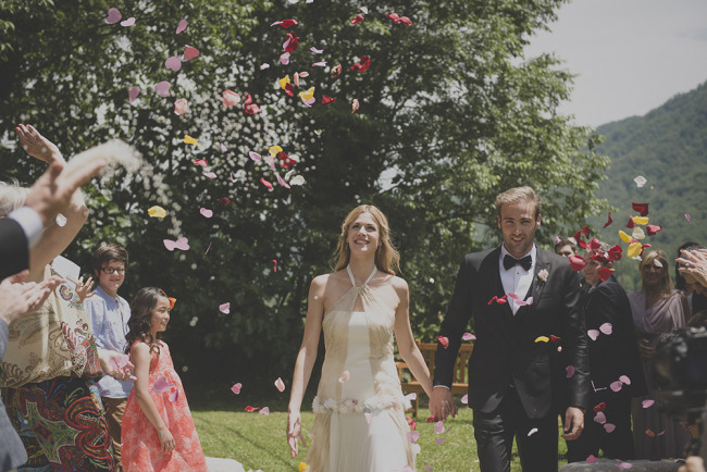 Bride and groom holding hands while walking down aisle; guests throw flower petals