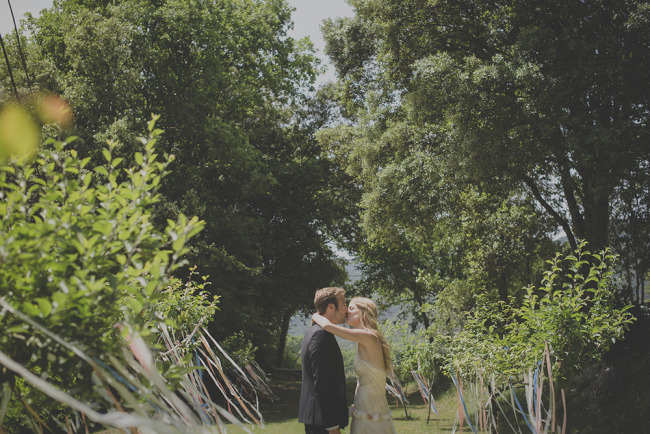 Bride and groom kissing between trees that have colorful ribbon hanging from them