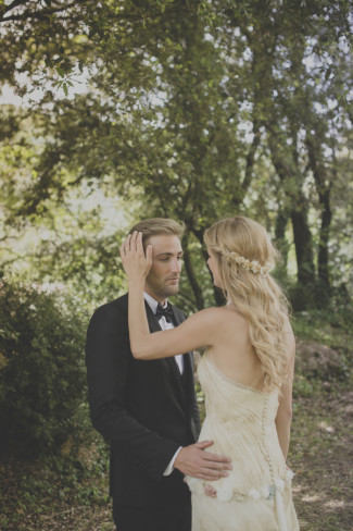 Groom with his hand on brides waist while she strokes his hair