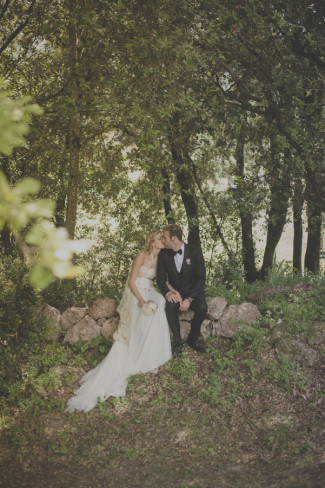 Bride and groom sitting on rocks while kissing