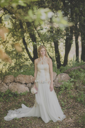 Bride wearing a Raimon Bundó gown with train standing in the forest