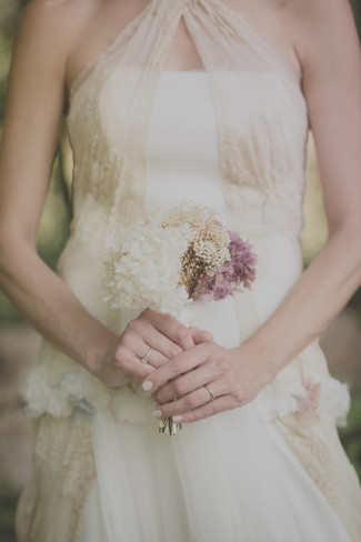 bride wearing a Raimon Bundó gown holding dried flowers