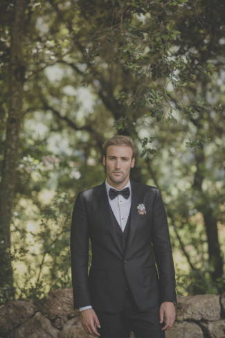 Groom wearing a classic black tux standing under a tree in private Spanish villa
