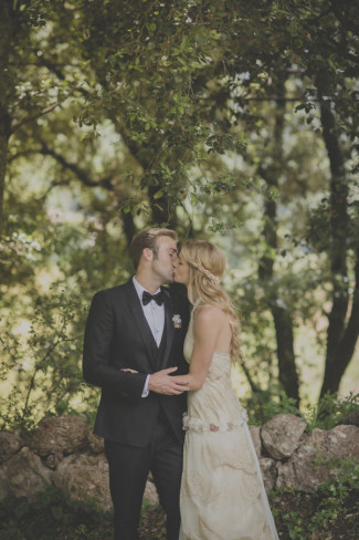 Bride wearing a Raimon Bundó gown and groom wearing tux kissing under a tree in Spain