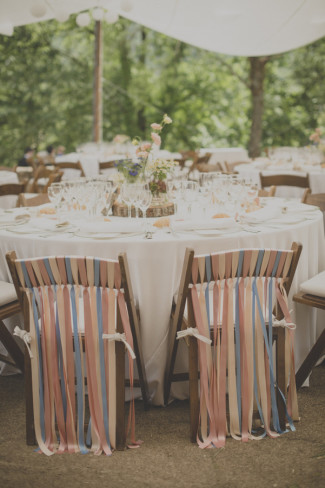 Bride and groom chair with colorful ribbon hanging from the back of the chair