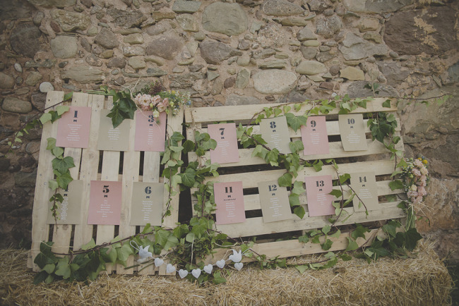 Pink and brown table number chart for guests on wooden crates
