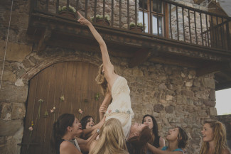 Bride performing a dance while a group of women pick her up