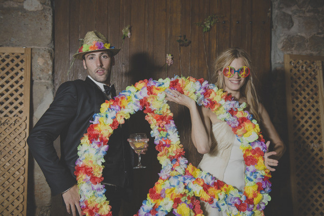 bride and groom in a photo booth wearing 60 peace glasses and holding a flower peace sign