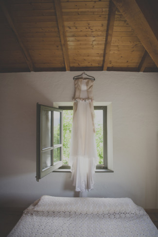 AvRaimon Bundó wedding gown hanging on hanger over bed