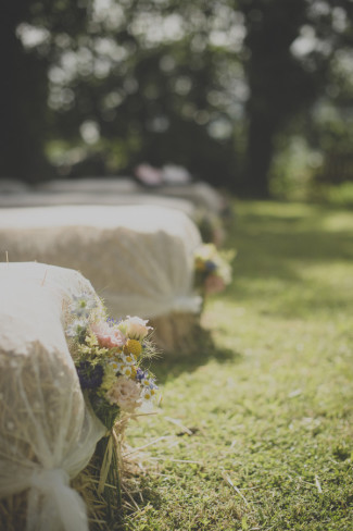 Hay bales as ceremony seating in outdoor wedding