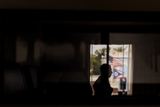 Groom getting ready in a dark room with a window and an american flag in the foreground