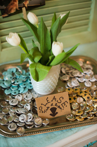 A silver tray of pins for wedding favors and a vase of white tulips