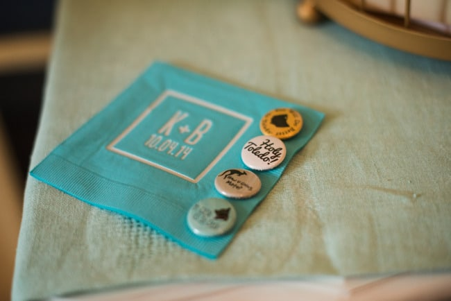 Teal napkin with the bride and grooms initials and wedding date and wedding favor pins
