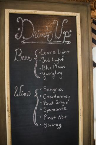 A chalkboard bar menu for a backyard wedding reception