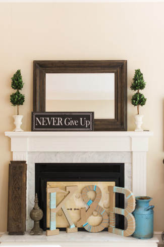 "A fireplace mantel with a ""never give up"" sign and two topiary trees and the bride and grooms initials on the floor"