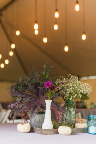Wedding reception under a white tent with purple and white floral center pieces