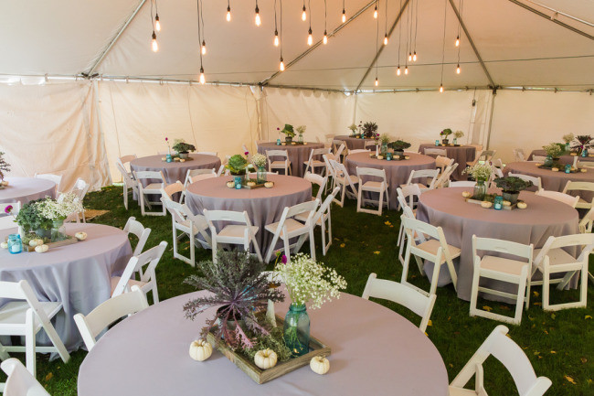 Backyard wedding reception with purple table cloths under a white tent