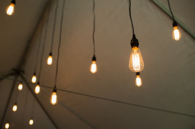 Old fashion Edison bulbs hanging from a white tent for wedding reception