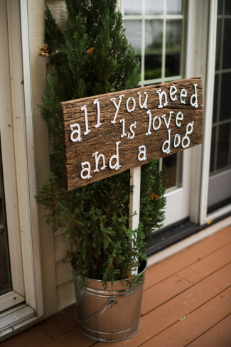 "A wooden sign with ""all you need is love and a dog"" in white writing"