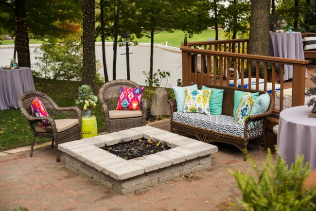 Backyard wedding reception with a fire bit and colorful throw cushions in wicker seating