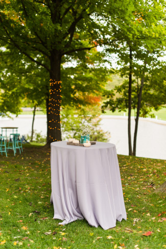 A high cocktail table with a purple table cloth for a backyard wedding reception
