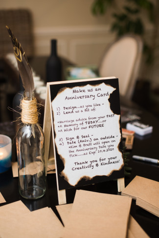 A miniature sandwich board asking guests to fill out anniversary cards for newlyweds