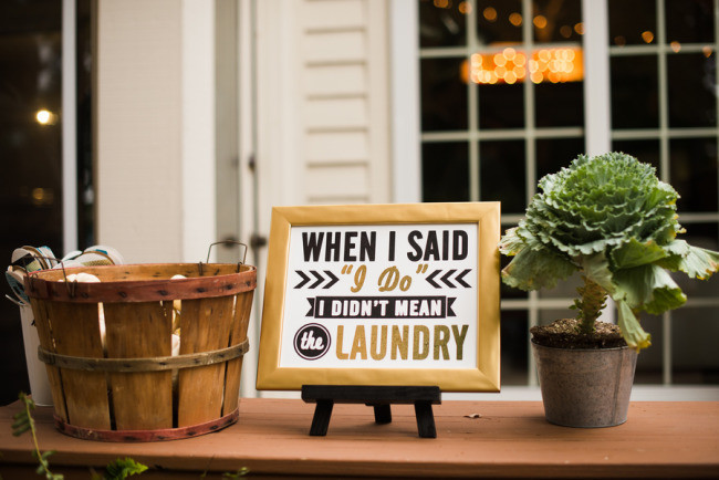 "A gold, black and white sign saying ""when I said I do I didn't mean the laundry"""