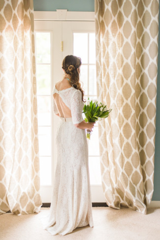 Bride wearing a Watters gown and holding a bouquet of white tulips