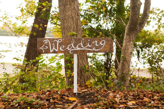 "Wooden sign saying ""Wedding"" with and arrow painted in white"