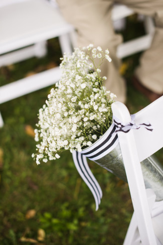Silver vase with baby's breath and a black and white ribbon as wedding ceremony aisle decor
